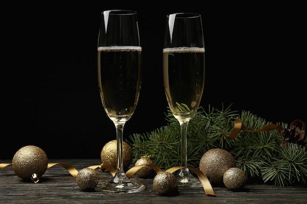 Copas de champán y accesorios de año nuevo en mesa de madera