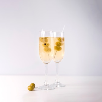 Copas de champán con aceituna aislado sobre fondo blanco.