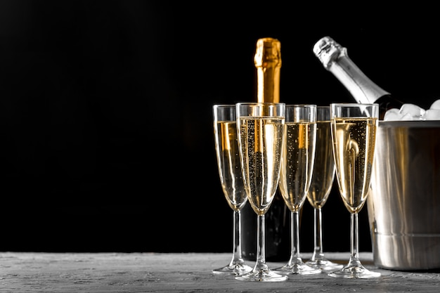 Copas de champán con una botella de champán en un balde