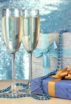 Copas de champán con cajas de regalo en la pared brillante