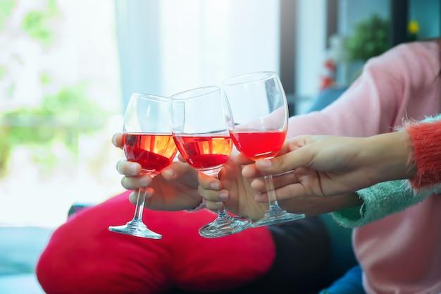 Copas de champán de cerca, celebración, comer y vacaciones, manos tintinear copas de vino, centrarse en manos tostado copa de vino tinto