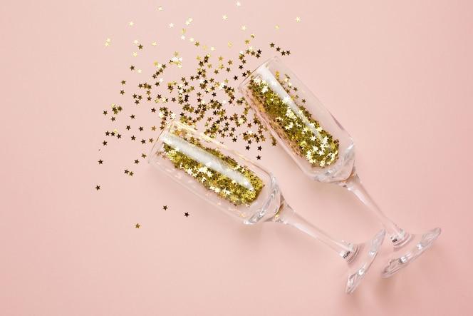 Copas de champán con confeti de estrellas doradas sobre beige