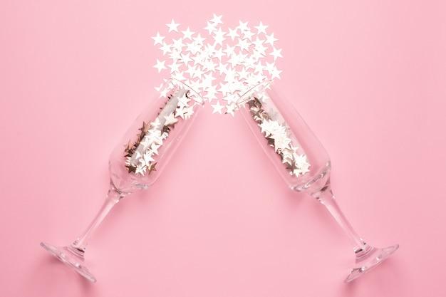 Copas de champán con confeti de estrellas plateadas sobre papel de color rosa estilo minimalista
