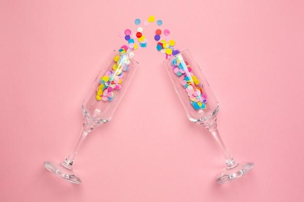 Copas de champán con confeti multicolor en rosa