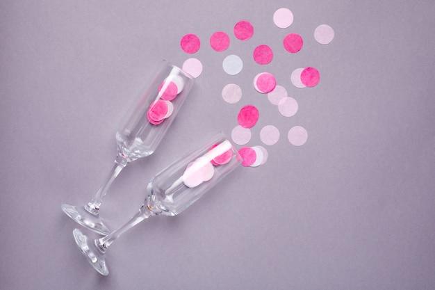 Copas de champán con confeti rosa sobre gris