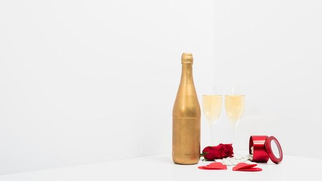 Copas de champán con corazones de papel rojo.
