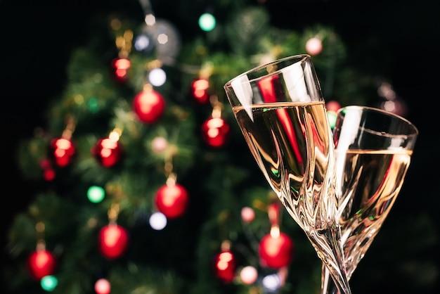 Copas de champán espumoso en el fondo de un árbol de navidad decorado.