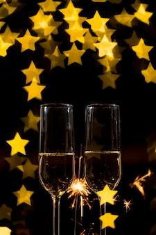 Copas de champán con fuegos artificiales y efecto bokeh en forma de corazón.