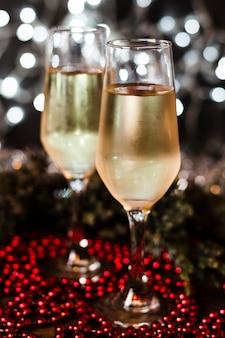 Copas de champán con luces de navidad en el fondo
