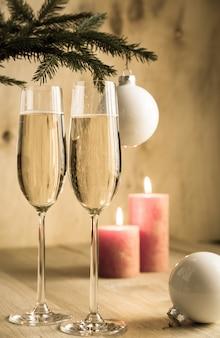 Copas de champán bajo la rama de un árbol de navidad decorado