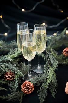 Copas de champán con ramas verdes en mesa