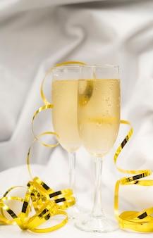 Copas de champán refrescante con serpentinas doradas sobre tela blanca