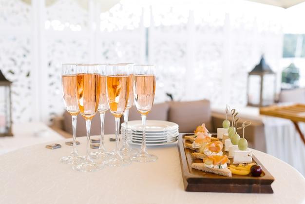 Copas de champán rosado se colocan en la mesa del buffet junto a un plato de aperitivos