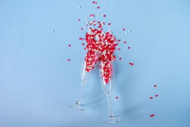 Copas de champán con salpicaduras de caramelo de azúcar en forma de corazón rojo. día de san valentín, aniversario o concepto de celebración de boda. endecha plana. vista superior. copia espacio