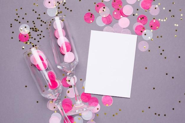 Copas de champán y tarjeta con confeti rosa