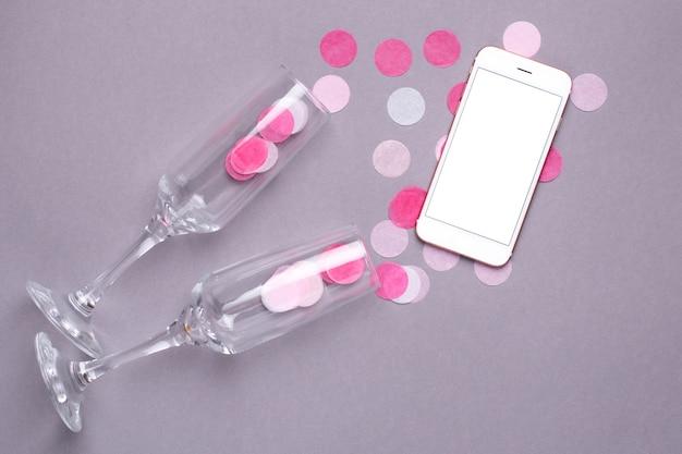 Copas de champán y teléfono móvil con confeti rosa sobre gris
