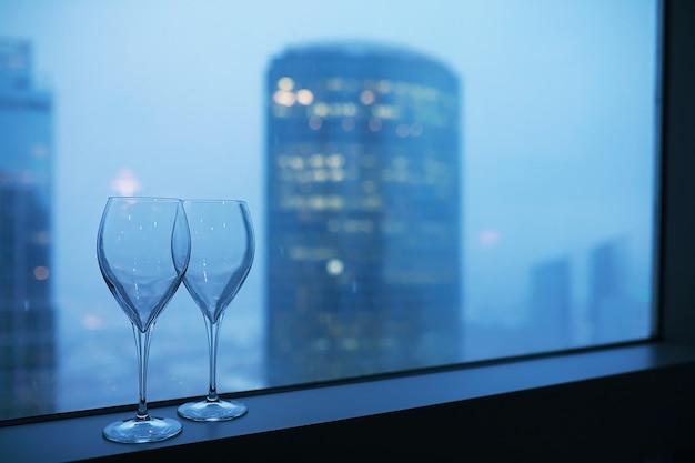 Copas de cóctel en el alféizar de la ventana por el cristal de un edificio alto
