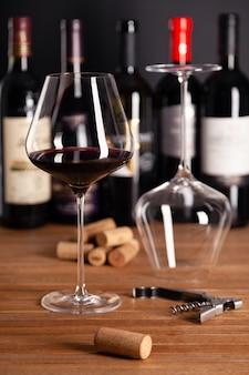 Copas de cristal de vino tinto, botellas, sacacorchos, corchos en mesa de madera