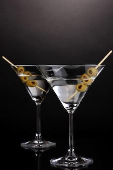 Copas de martini y aceitunas sobre fondo gris