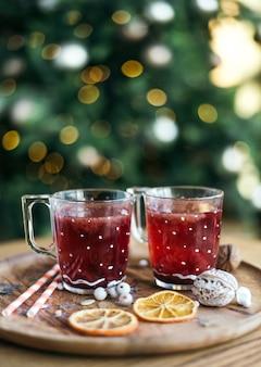 Copas de té y vino caliente de navidad, composición festiva. decoración sobre una mesa de madera y un árbol de navidad decorado. ambiente de imagen de tradición.