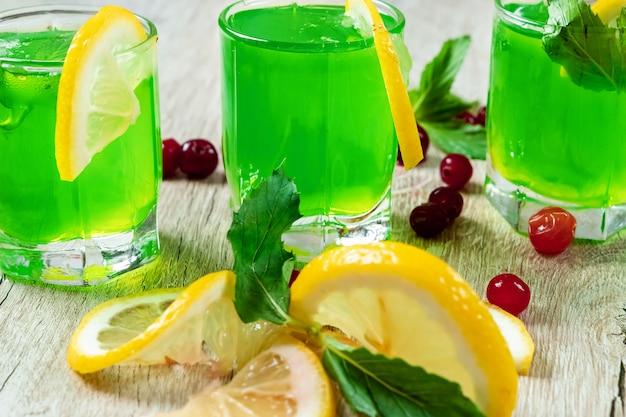 Copas verdes copas alcohólicas frío cóctel con arándanos frambuesas limón y menta