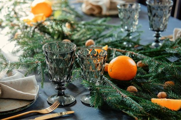Copas de vidrio sobre la mesa junto a un plato y abeto en navidad