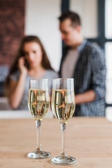 Copas de vino blanco y pareja en casa.