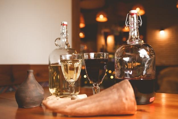 Copas de vino y botellas de vino tinto y blanco sobre la mesa en casa oscura sala de estar en el fondo.