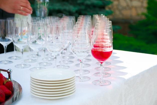 Copas de vino, champán, platos y bayas en el mantel blanco