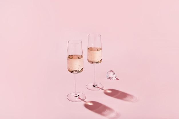 Copas de vino espumoso sobre fondo de color rosa con sombras afiladas