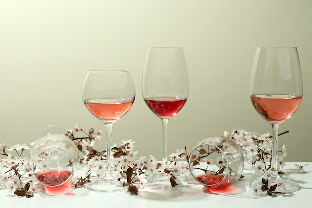 Copas de vino y flores de cerezo en mesa blanca