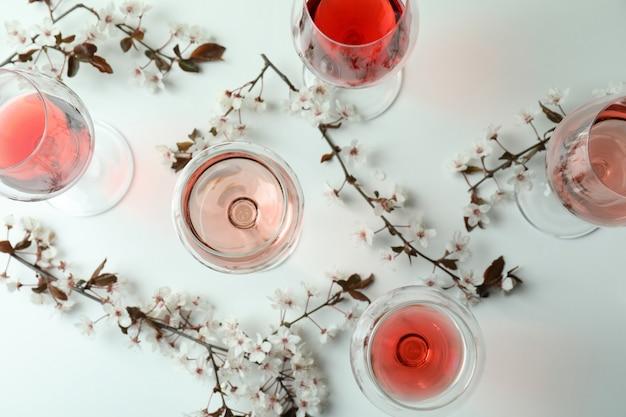 Copas de vino y flores de cerezo sobre fondo blanco.
