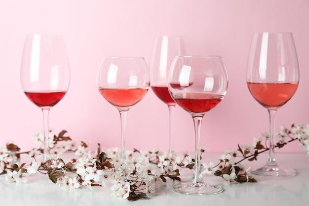 Copas de vino y flores de cerezo sobre fondo rosa