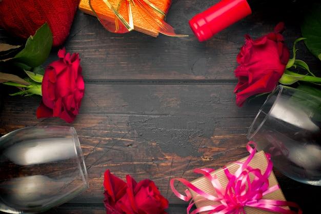 Copas de vino y flores color de rosa en la mesa de madera