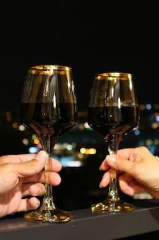 Copas de vino en manos de una pareja feliz con la vista nocturna en telón de fondo
