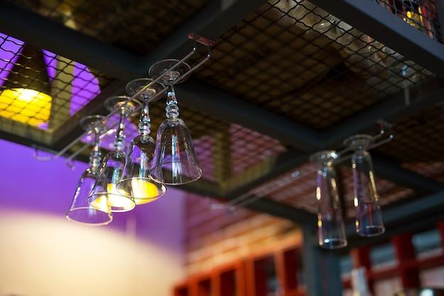 Copas de vino o cócteles vacías cuelgan de la barra de un bar o pub.