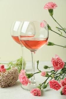 Copas de vino rosado y hermosas flores.