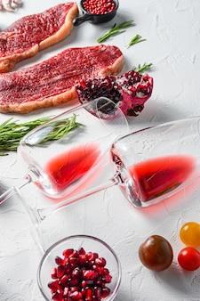 Copas de vino tinto con condimentos y bistec de ternera