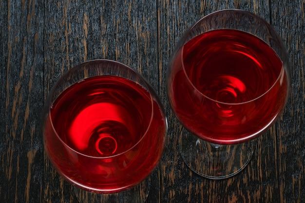 Copas de vino tinto en una mesa de madera negra, vista superior.