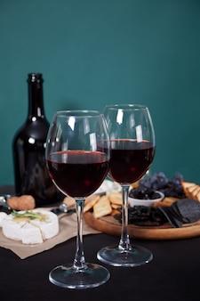 Copas de vino tinto y plato con variedad de quesos, frutas