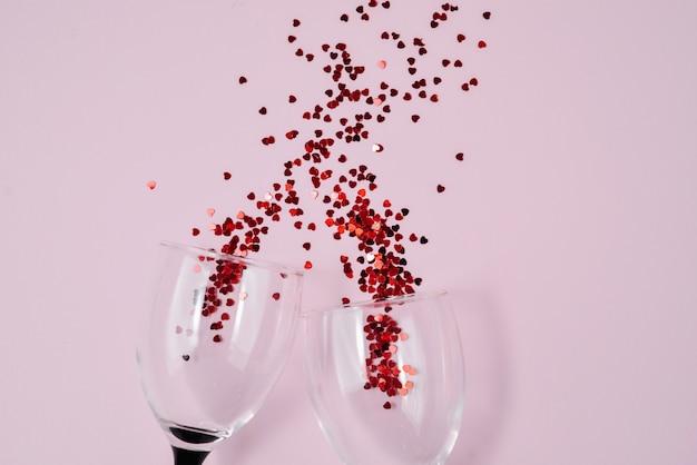 Las copas de vino vertieron confeti rojo del corazón en fondo rosado del papel del color.