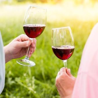 Copas de vino con vino tinto en manos de la pareja en picnic