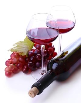 Copas de vino con vino tinto, uva y botella aislado en blanco