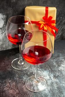 Copas de vista frontal de regalo de vino sobre fondo oscuro