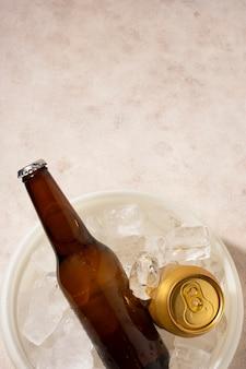 Copia espacio batalla de cerveza y lata en cubo con cubitos de hielo