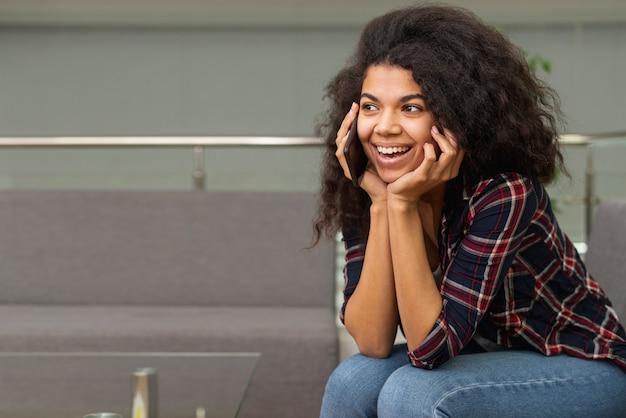 Copia-espacio chica en la biblioteca hablando por teléfono