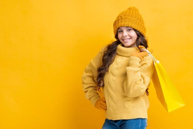 Copia espacio chica con bolsa de ropa de compras de invierno