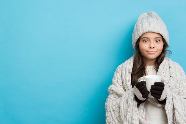 Copia-espacio chica en invierno bebiendo té caliente