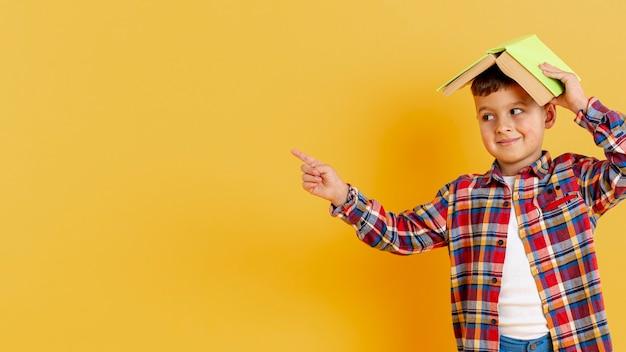 Copia-espacio chico con libro en cabeza apuntando