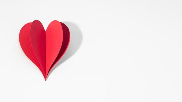 Copia-espacio corazón de papel rojo en la mesa